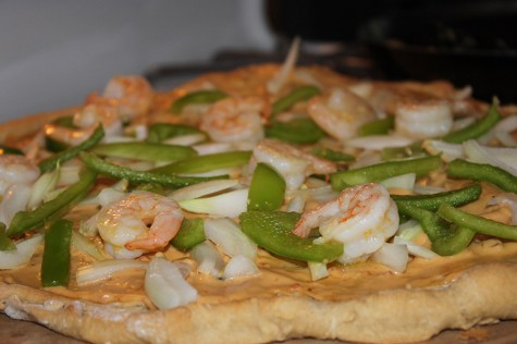 Evenly place shrimp, peppers, and onions onto pizza crust.