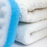 Blue massage sponge against white towels