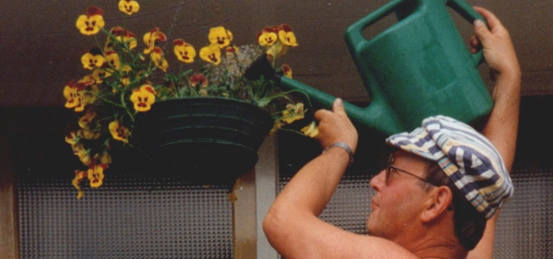 Watering A Hanging Basket Overhead with a watering can