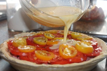 Rustic garden tomato pie with ham, egg, onions, and cheese